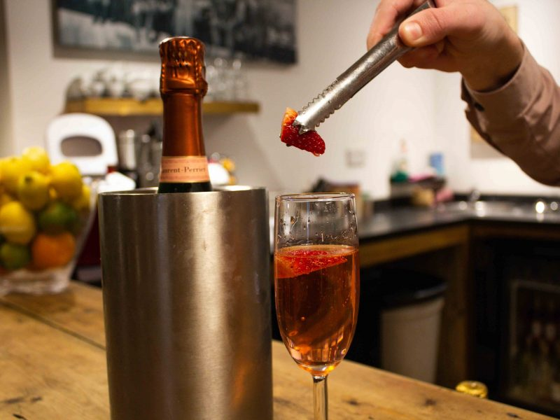 Larent Perrier Rose champagne in glass and cooler strawberries dropped in glass