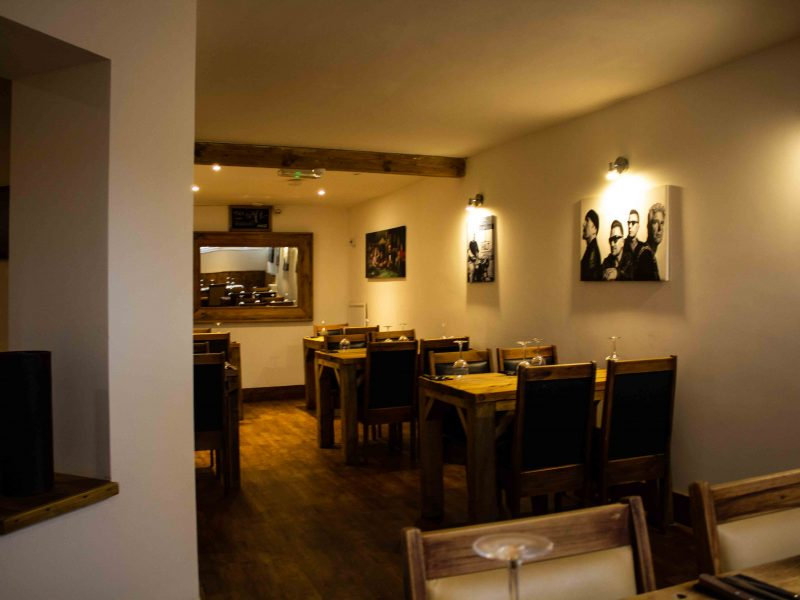 Shot of bespoke wooden tables in back-section of the restaurant.